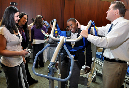 From left, OT students Kate Wisnieski, Erica Smith and Ed Egonmwan talk with John Kruse of Prism Medical about his 'Sit to Stand' lift during the 1st Annual Multidisciplinary Safe Patient Handling Workshop.