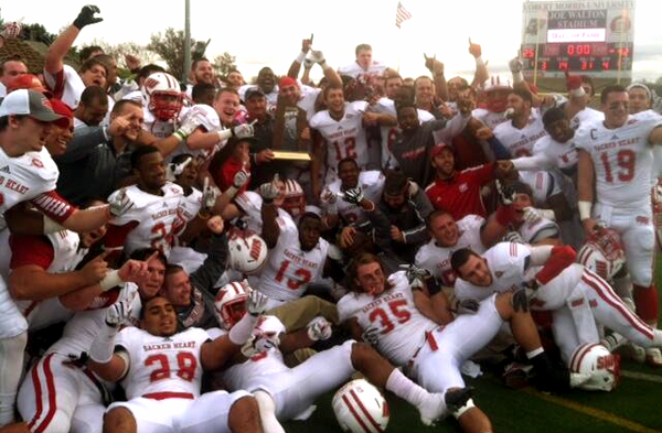 The football team celebrates winning the NEC Championship.